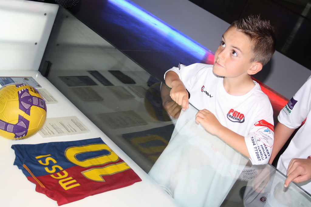 Young boy looking at football kit - tours